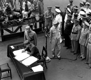 General Hsu Yung Chang 徐永昌 (Xu Yongchang) signing the &quoteJapanese Instrument of Surrender&quote on the weather deck of the USS Missouri BB-63, 2 September 1945, with the Supreme Allied Commander, General Douglas MacArthur standing at right